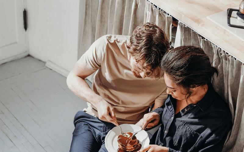 一緒に食べている男女の画像