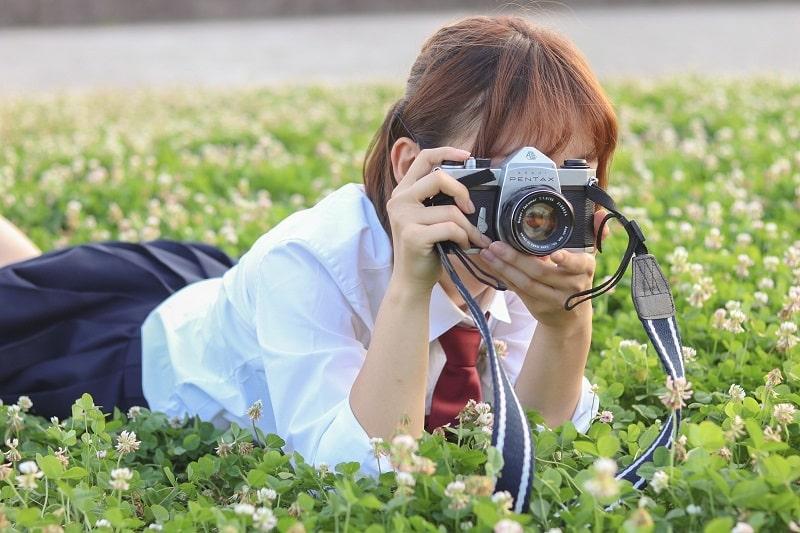 カメラで風景を撮る女性の画像