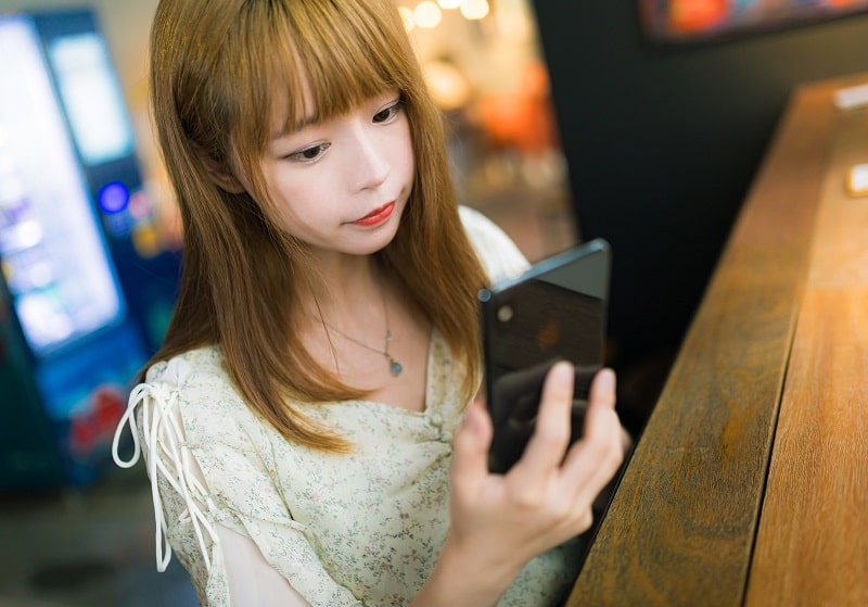 携帯でマッチングアプリをする女性の画像